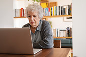 concentrated senior woman browsing internet laptop