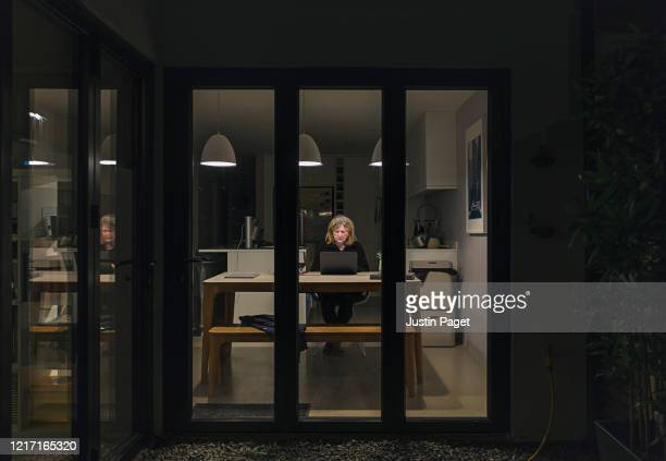 senior woman using laptop at night - photographed through window stock pictures, royalty-free photos & images