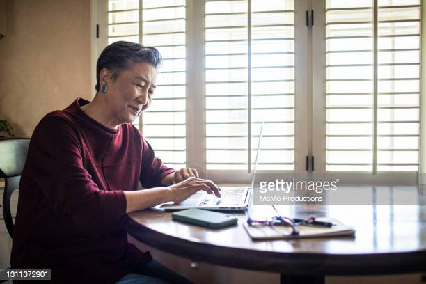 senior woman using laptop computer at home - scammer stock pictures, royalty-free photos & images