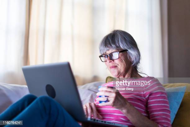 senior woman using laptop computer to speak to friends from home - looking at camera stock pictures, royalty-free photos & images