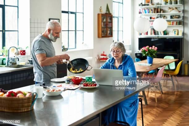 Senior woman using laptop in kitchen as man serves breakfast