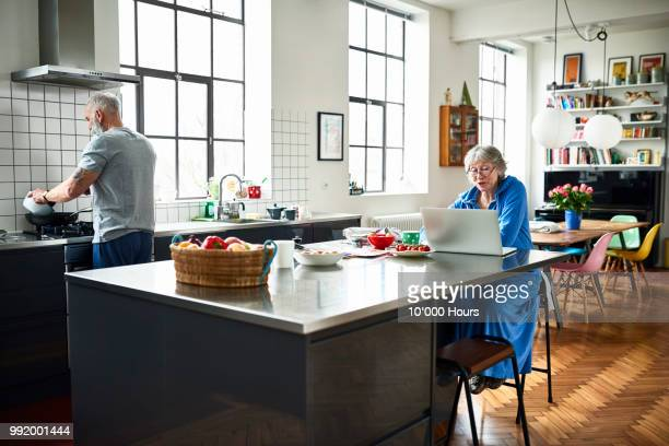 Senior woman using laptop in kitchen with man cooking dinner
