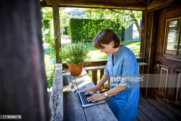 senior woman using laptop on porch of a rustic wooden hut - young at heart woman fotografías e imágenes de stock