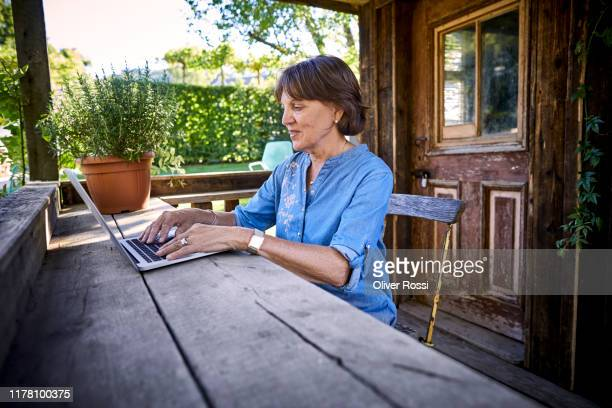 senior woman using laptop on porch of a rustic wooden hut - one senior woman only stock pictures, royalty-free photos & images