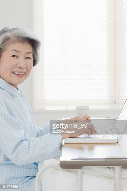 Senior woman using laptop PC in hospital bed