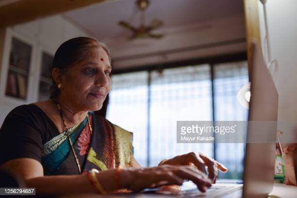 senior woman using laptop - concentration stock pictures, royalty-free photos & images