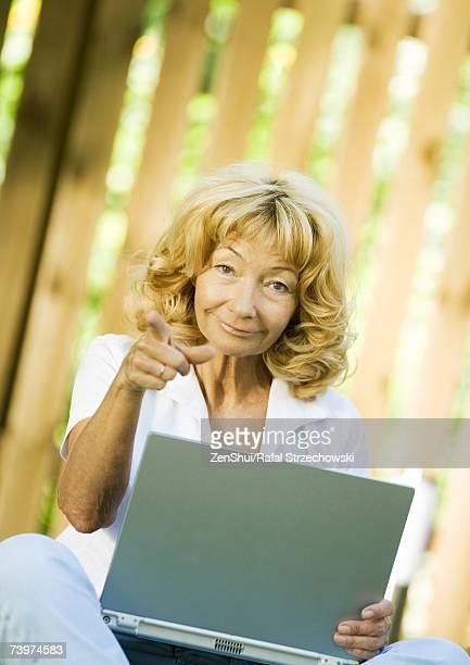 Senior woman using laptop, pointing at camera