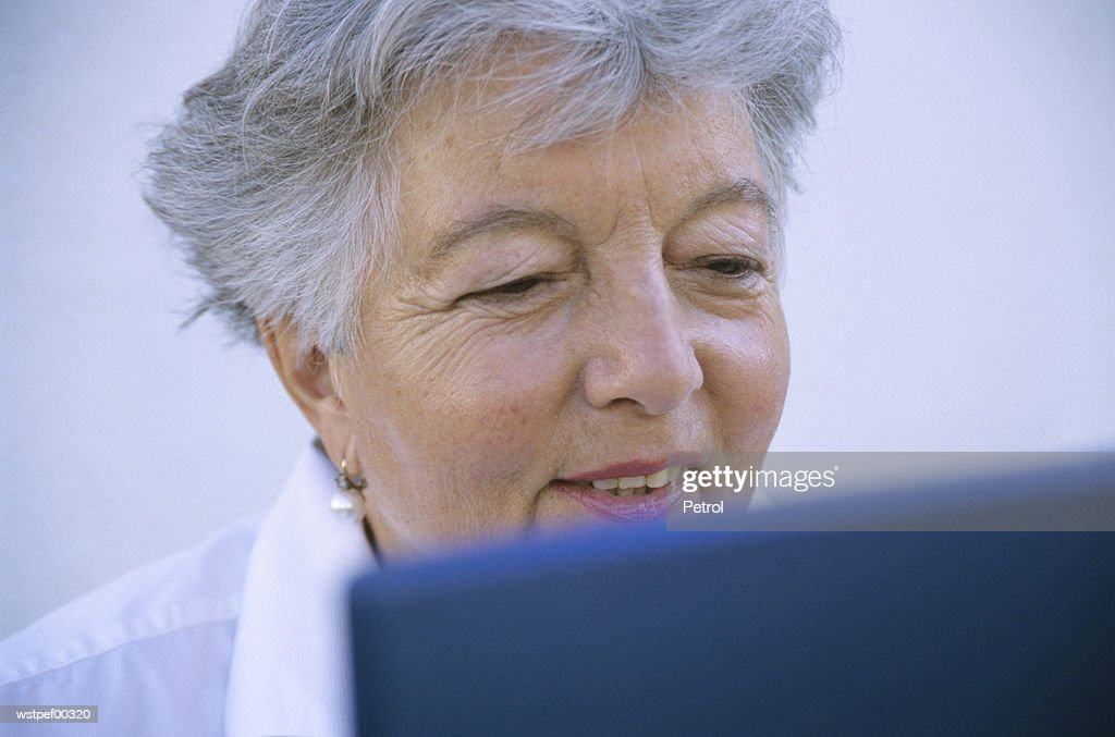 Senior woman using laptop, smiling : Stockfoto