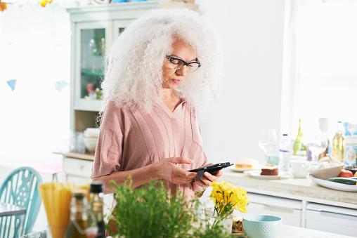 senior woman using mobile phone in kitchen - gettyimageskorea