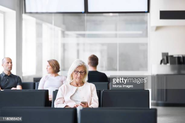 senior woman using mobile phone in waiting room - waiting room stock pictures, royalty-free photos & images