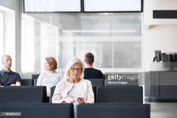 seniorin mit handy im wartezimmer - wartezimmer stock-fotos und bilder