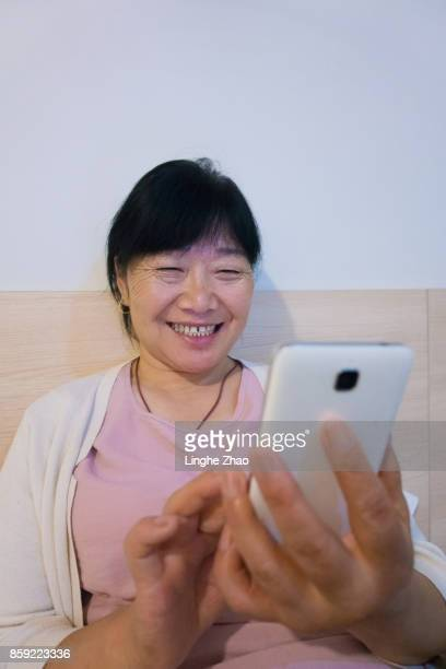 Senior woman using mobile phone on bed