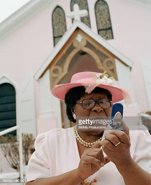 senior woman using mobile phone outside church - 一張羅 ストックフォトと画像