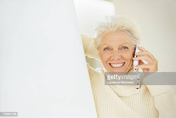 Senior woman using mobile phone, smiling, portrait