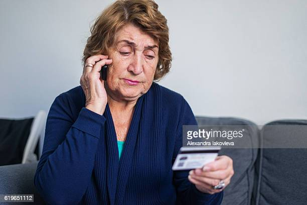 senior woman using mobile phone while holding credit card - fraud stock pictures, royalty-free photos & images