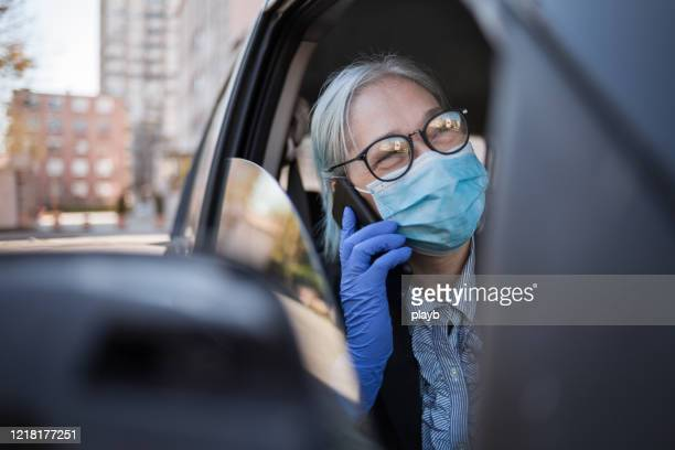 senior woman using phone in the car - driving mask stock pictures, royalty-free photos & images