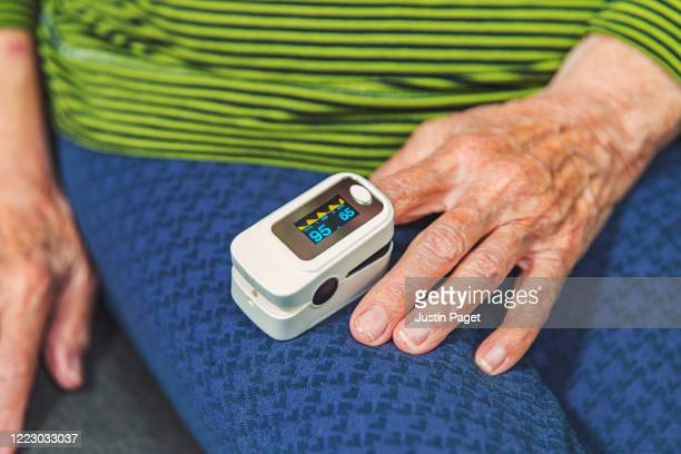 senior woman using pulse oximeter - pulse oximeter stock pictures, royalty-free photos & images