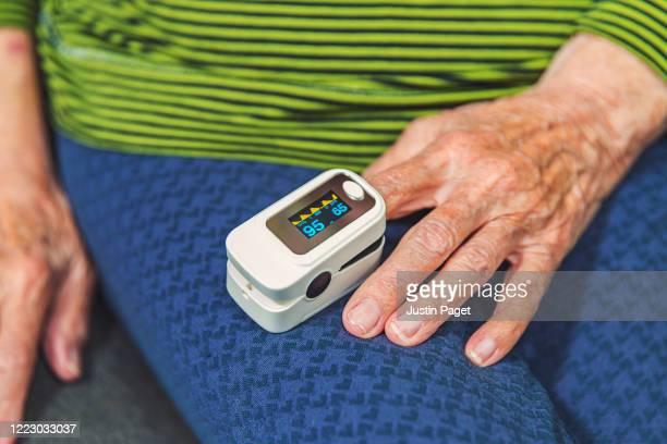 senior woman using pulse oximeter - 状態 ストックフォトと画像
