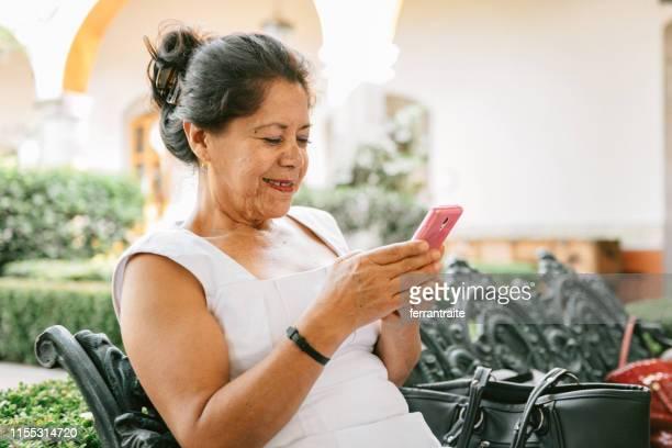 mujer senior usando teléfono inteligente - mujeres mexicanas fotografías e imágenes de stock