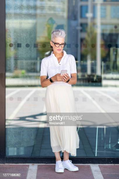 senior woman using smart phone while standing against glass window on footpath - one senior woman only stock pictures, royalty-free photos & images