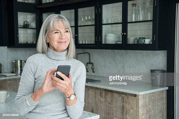 senior woman using smartphone in modern kitchen - 60 64 years stock pictures, royalty-free photos & images