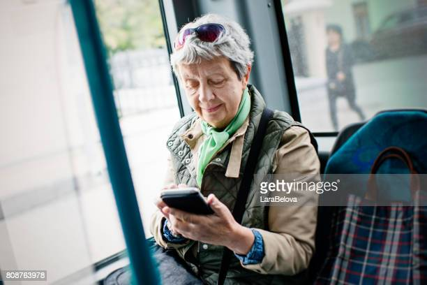 Senior woman using smartphone in the bus