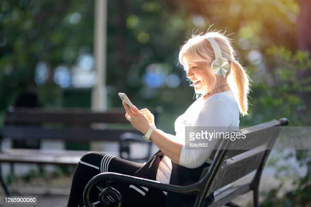 senior woman using smartphone in the public park - mental wellbeing stock pictures, royalty-free photos & images