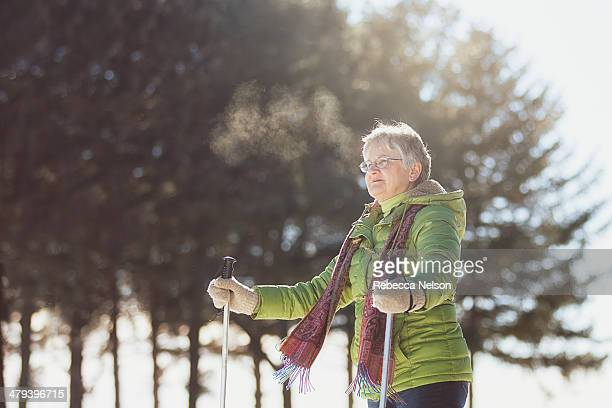 senior woman using snow shoes - green coat stock pictures, royalty-free photos & images