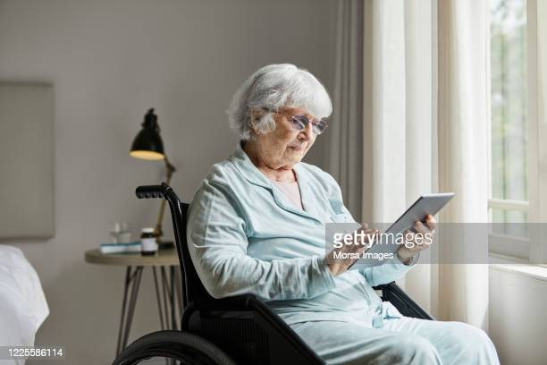senior woman using tablet pc at home - document stock pictures, royalty-free photos & images