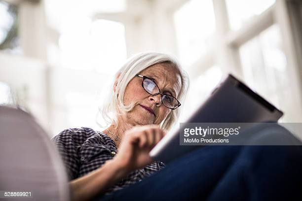 senior woman using tablet - tablet benutzen stock-fotos und bilder