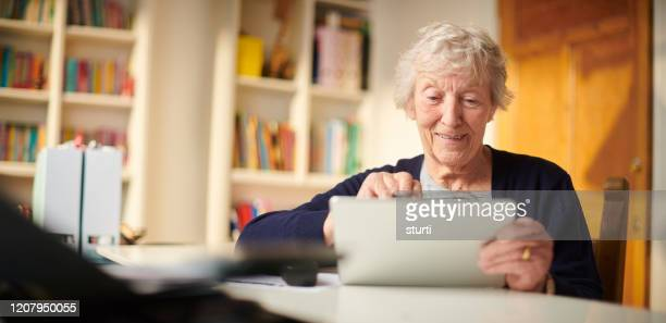 senior woman using the web to keep in touch - senior women stock pictures, royalty-free photos & images