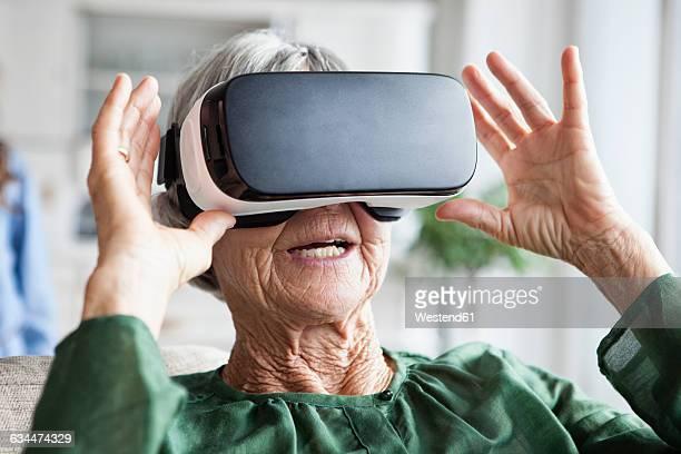 Senior woman using Virtual Reality Glasses at home