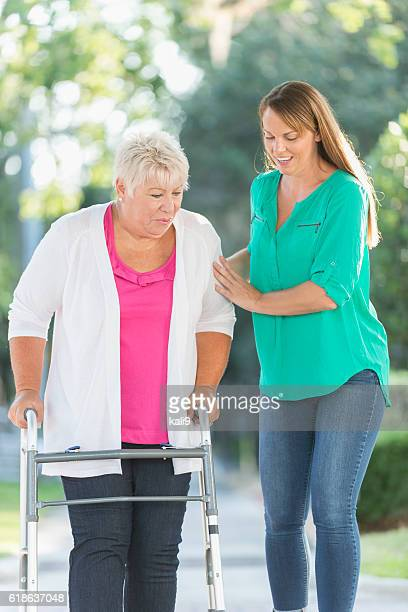 Senior woman using walker, helped by adult daughter