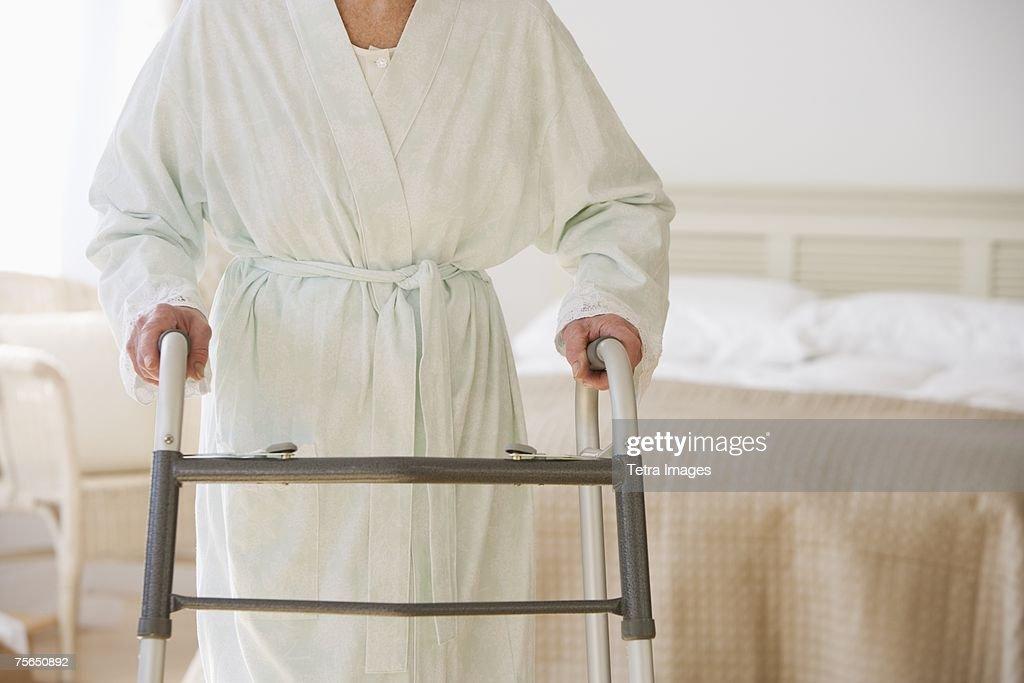 Senior woman using walker in bedroom : Stock Photo