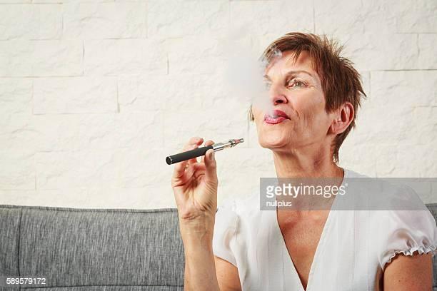 Senior woman vaping, enjoying an electronic cigarette