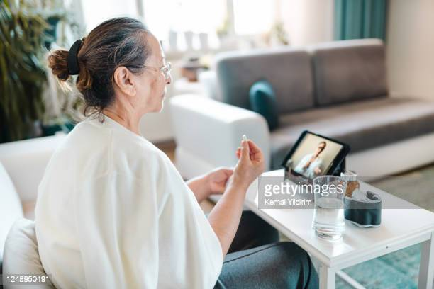 senior woman video calling with female healthcare person - turkey middle east stock pictures, royalty-free photos & images