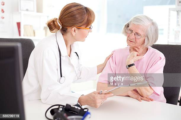 senior woman visiting doctor. - bezoek stockfoto's en -beelden