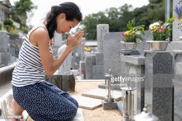 mujer mayor visitando tumba familiar - mausoleo fotografías e imágenes de stock