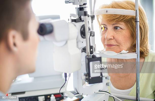 senior woman visiting optician. - optometry stock pictures, royalty-free photos & images
