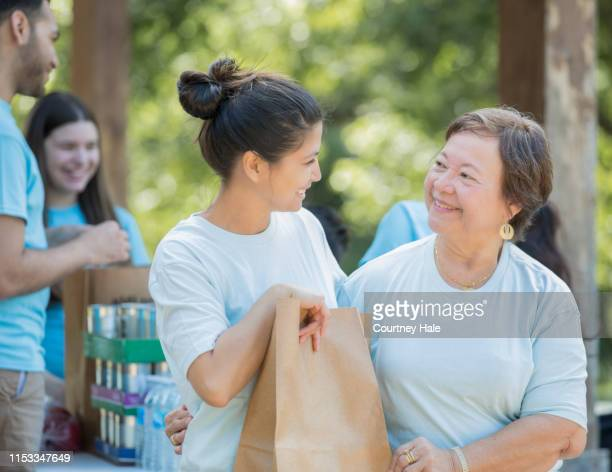 senior woman volunteering at food drive with diverse community group - selfless stock pictures, royalty-free photos & images