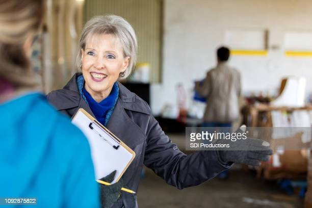senior woman volunteers in food bank - homeless shelter stock pictures, royalty-free photos & images