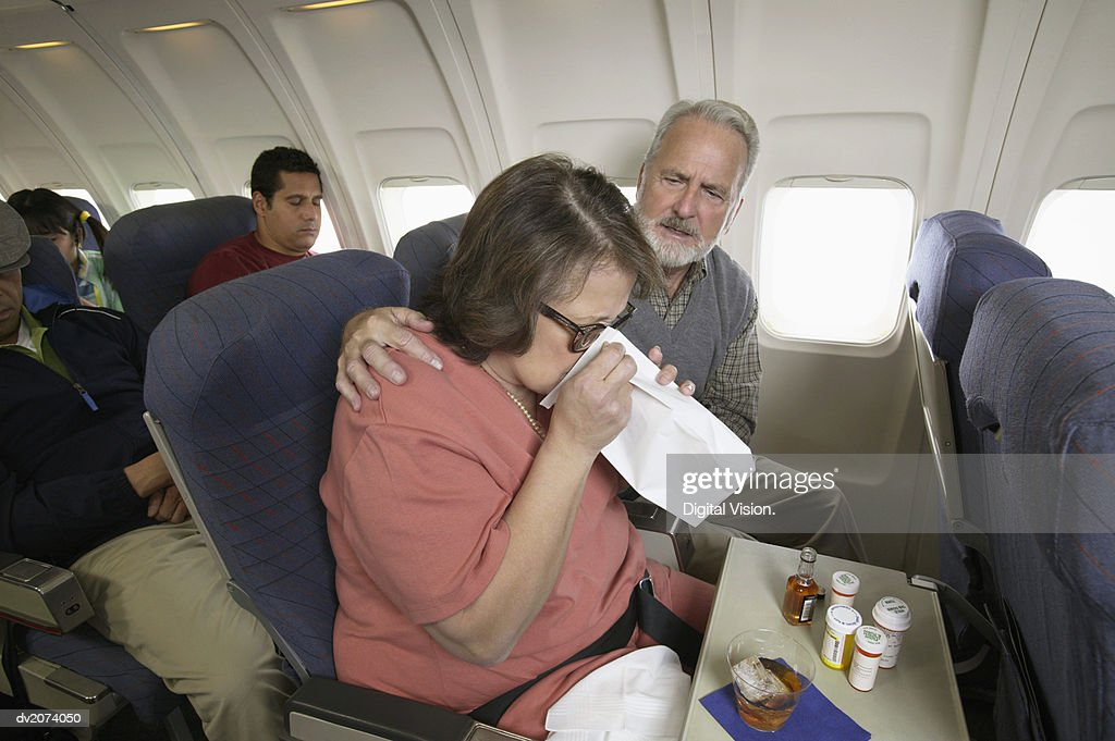 Senior Woman Vomiting Into a Sick Bag During a Flight on a Plane : Stock Photo