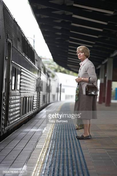 Senior woman waiting on station platform holding handbag