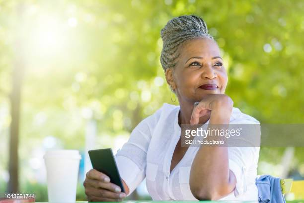 senior woman waits for friend in public park - looking away stock pictures, royalty-free photos & images
