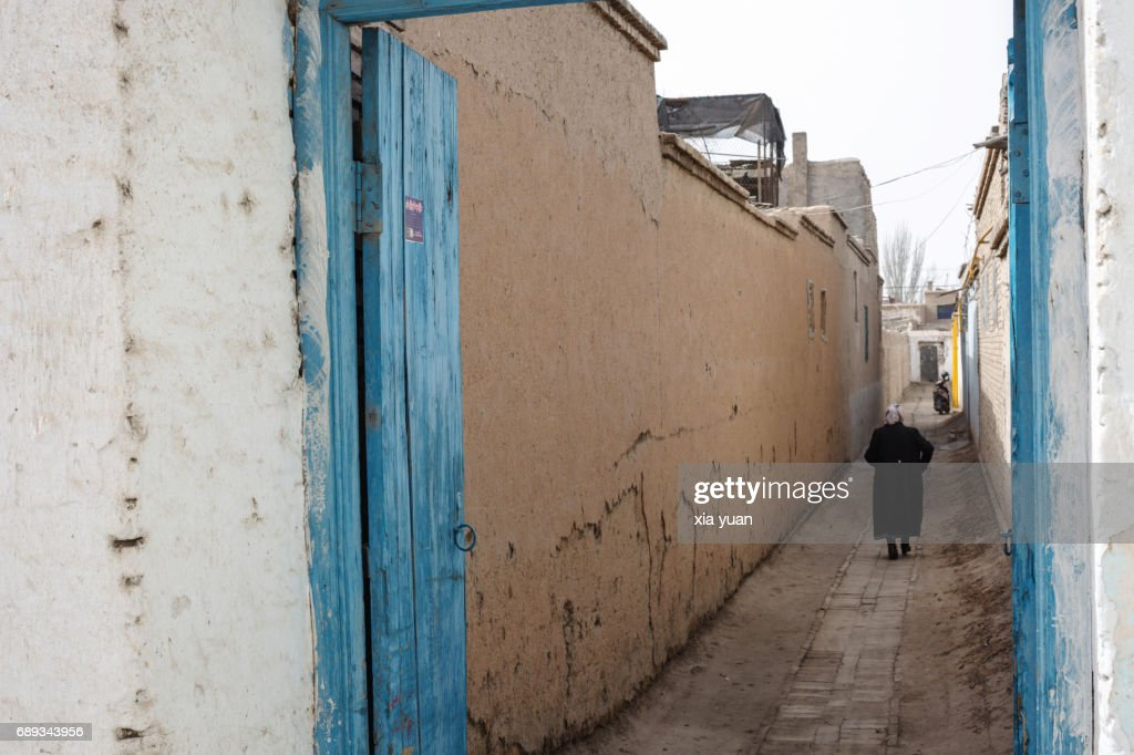 Senior woman walking along alley admist mud-brick houses in Kuqa,China : Foto de stock