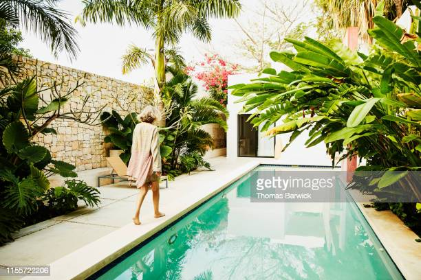 senior woman walking along edge of pool at tropical spa - image stock pictures, royalty-free photos & images