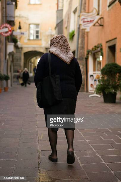 senior woman walking down narrow street in old historical city - old women in pantyhose stock photos and pictures