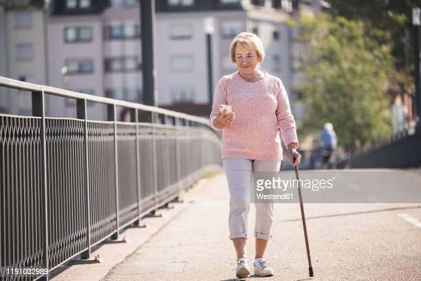 senior woman walking on footbridge, using walking stick - leaning disability stock pictures, royalty-free photos & images