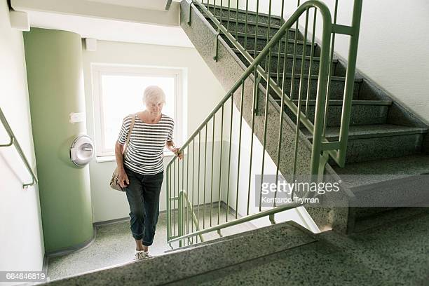 senior woman walking on staircase in apartment building - escaleras fotografías e imágenes de stock