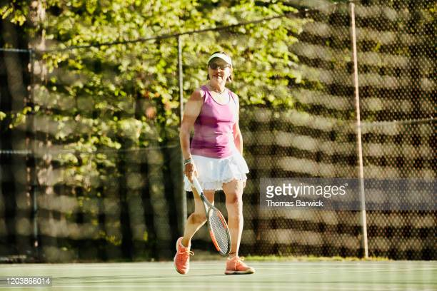 Senior woman walking on to tennis court for early morning match